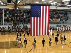 Daleville High School cheerleaders surround the flag during the National Anthem
